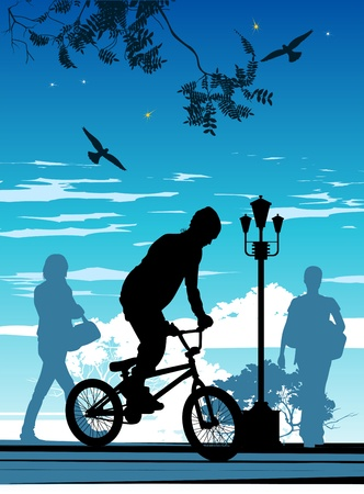 young man standing: young man standing on a bicycle in front of people