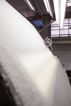 fabric roll: white fabric sliding over a quality controll lamp. with a counting machine measuring the length of a textile piece roll. production of fine woolen fabrics for suits - in a factory in Sabadell, Spain Stock Photo