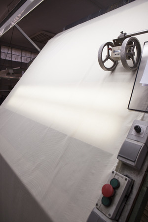 thread count: white fabric sliding over a quality controll lamp. with a counting machine measuring the length of a textile piece roll. production of fine woolen fabrics for suits - in a factory in Sabadell, Spain Editorial