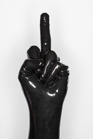 sexual anatomy: gesture of a hand wearing a black latex glove. middle finger Stock Photo