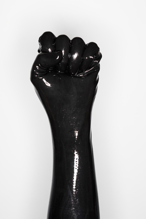 sexual anatomy: gesture of a hand wearing a black latex glove: fist Stock Photo