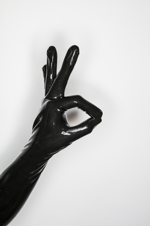 sexual anatomy: gesture of a hand wearing a black latex glove, signalling ok