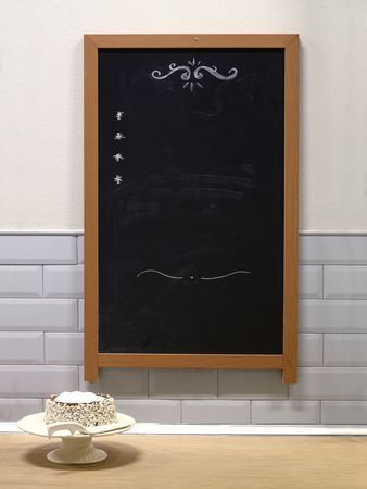 things that go together: White cake and chalk board with the menu Stock Photo