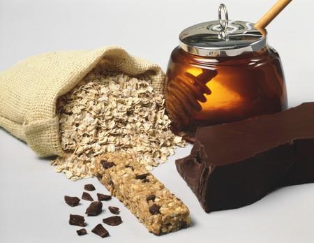 avena en hojuelas: Naturaleza muerta con copos de avena. barra de muesli. chocolate y miel