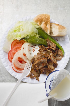 ner: D�ner kebab with vegetables on paper plate. drinking yoghurt