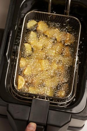 fryer: Potatoes being fried in a deep fat fryer