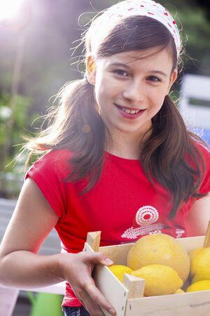 감귤류의 과일: A girl holding a crate of citrus fruits LANG_EVOIMAGES