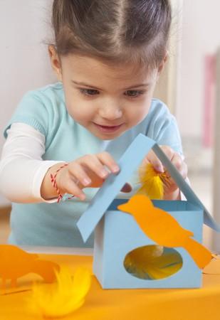 maison oiseau: Une petite fille faire une maison de papier d'oiseaux