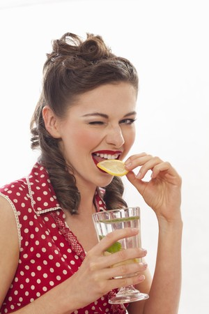 A retro-style girl eating a slice of lemon from a glass of lemonade