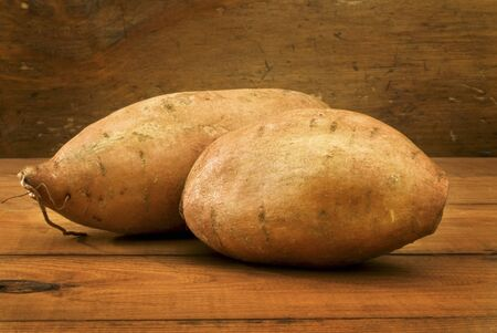 tuberous: Two Sweet Potatoes on Wooden Table LANG_EVOIMAGES