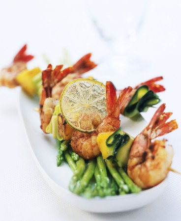 cocozelle: Scampi kebabs with courgette on green asparagus