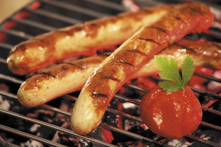 grilled sausages: Grilled sausages and tomatoes on a barbeque