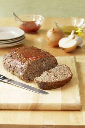 pastel de carne: Parcialmente en rodajas del pan con carne en la tarjeta de corte; Platos y Ingredientes
