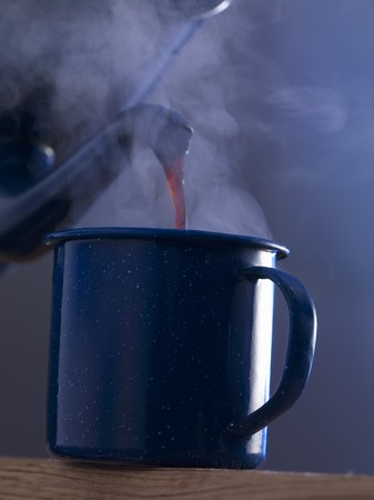 coffeepots: Coffee being poured into an enamel mug LANG_EVOIMAGES