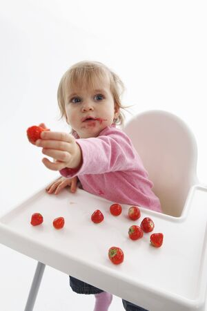A small child with strawberries LANG_EVOIMAGES