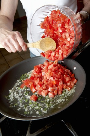 sautee: Woman Adding Fresh Diced Tomatoes into a Skillet on the Stove