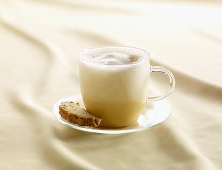eggnog: Ponche de huevo con especias en una taza de vidrio con biscotti