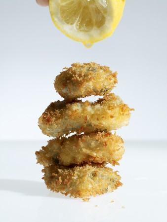 'main squeeze': Breaded oysters being drizzled with lemon juice