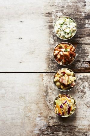 contorni: Piatti Barbecue laterali in piccole ciotole su un tavolo in legno; Carne di maiale e fagioli, insalata di patate, insalata di cavolo e Succotash LANG_EVOIMAGES
