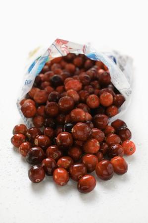 vaccinium macrocarpon: Fresh cranberries falling out of plastic bag
