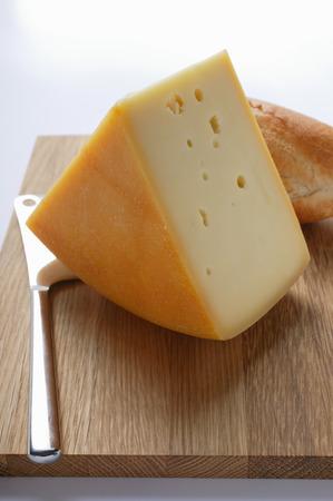 se: Piece of Bergkäse with baguette on chopping board LANG_EVOIMAGES
