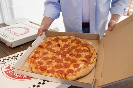 pizza box: Hombre que sostiene la caja de pizza que contiene la pizza de pepperoni