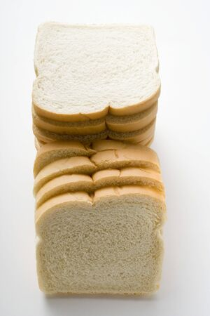 several breads: White sliced bread, in a pile