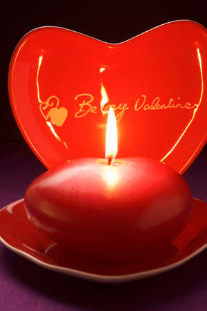 Red candle and heart-shaped plate for Valentines Day LANG_EVOIMAGES