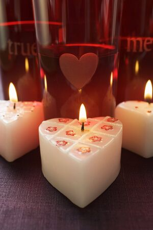 votive: Burning heart-shaped candles for Valentines Day