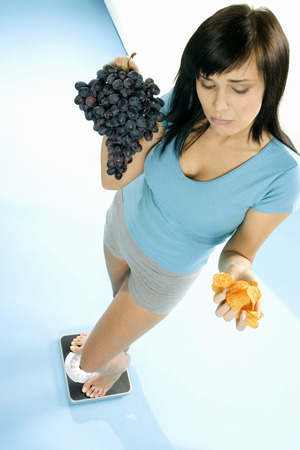 body consciousness: Young woman standing on scales with crisps and grapes LANG_EVOIMAGES