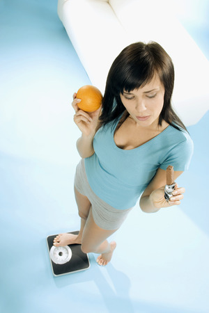 25 to 30 year olds: Young woman standing on scales with chocolate bar & orange