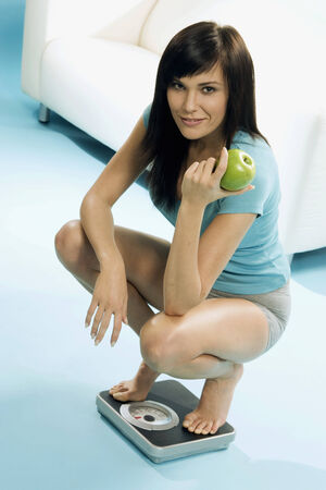 body consciousness: Young woman with apple in hand squatting on scales