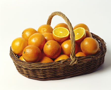 willow fruit basket: Fresh oranges in a shallow wicker basket LANG_EVOIMAGES
