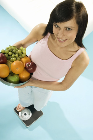25 to 30 year olds: Young woman standing on scales with bowl of fruit