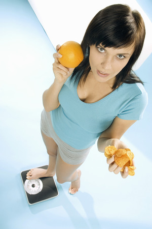 enquiring: Young woman standing on scales with crisps and orange