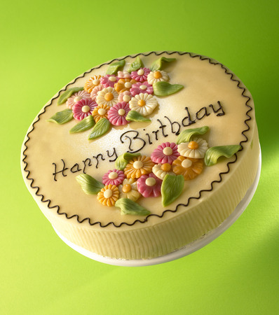 entire: Cake with marzipan flowers and the words Happy Birthday