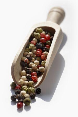 wooden scoop: Coloured peppercorns in a wooden scoop