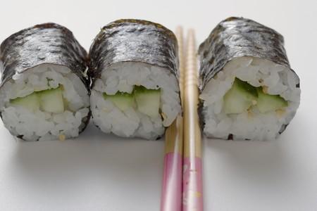maki sushi: Trois sushi maki au concombre et des baguettes