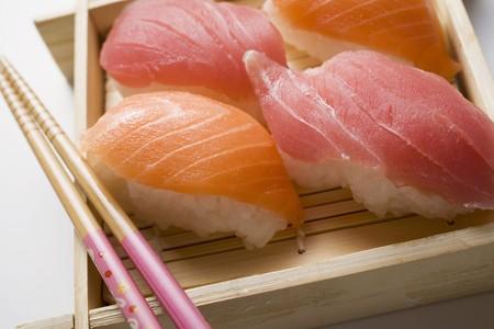 bamboo mat: Nigiri sushi with chopsticks on bamboo mat LANG_EVOIMAGES