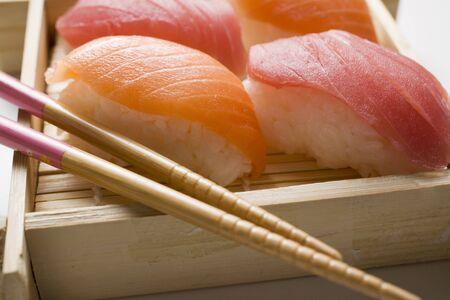 tunafish: Nigiri sushi with chopsticks on bamboo mat LANG_EVOIMAGES