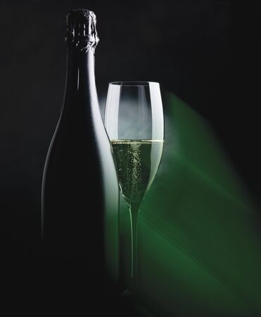champers: Bottle and glass of sparkling wine in green light