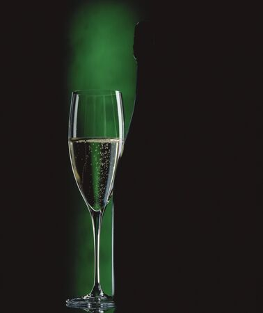 champers: Glass of sparkling wine beside wine bottle in green light