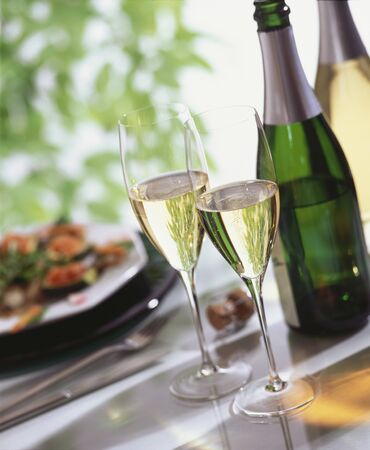 Glasses of sparkling wine, wine bottle, stuffed courgettes