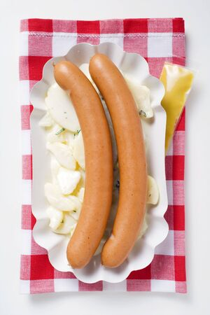scalded sausage: A pair of frankfurters on potato salad