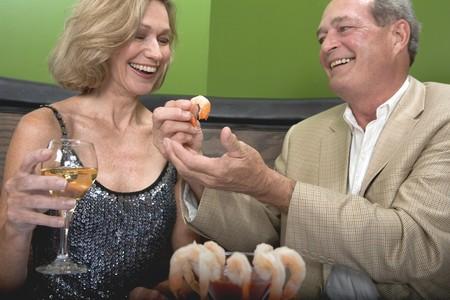 gorging: Man and woman eating shrimps in restaurant