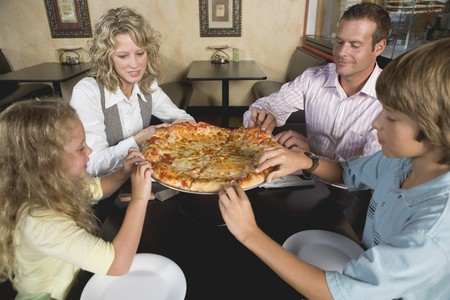 Family in restaurant sharing pizza LANG_EVOIMAGES