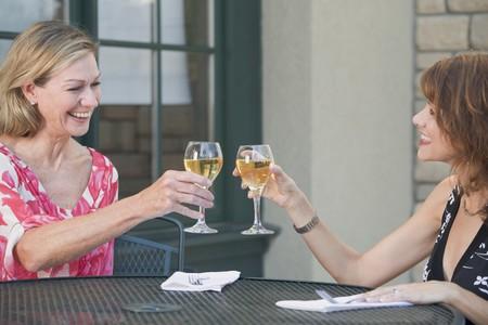conviviality: Two women raising glasses of white wine