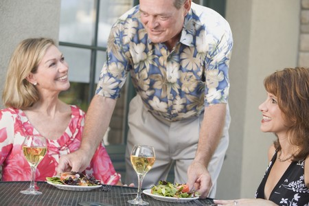 Man serving two women with plates of salad