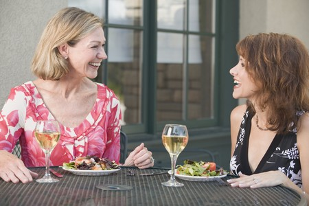 connoisseurs: Two women with salad and wine at table on a terrace LANG_EVOIMAGES