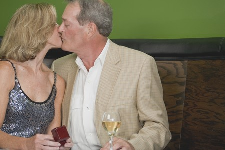 conviviality: Mature couple kissing in a restaurant
